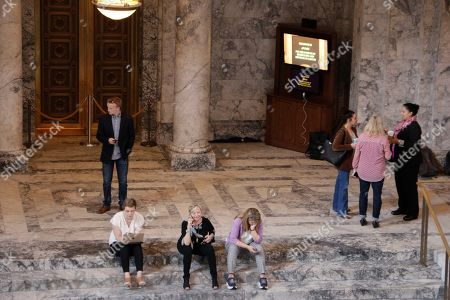 Stock Photo of Lobbyists and others are seen waiting in the Capitol rotunda ahead of floor votes in the House and Senate,, in Olympia, Wash. State lawmakers are wrapping up a 105-day legislative session in which they were tasked with passing a new, two-year state budget