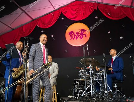Branford Marsalis, left, Delfeayo Marsalis, front, and Wynton Marsalis listen as James Black plays the drums in the Ellis Marsalis Family Tribute performance in the Jazz Tent during the New Orleans Jazz & Heritage Festival in New Orleans