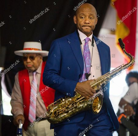 Branford Marsalis walks onto the Jazz Tent stage ahead of his father Ellis Marsalis before the Ellis Marsalis Family Tribute performance during the New Orleans Jazz & Heritage Festival in New Orleans
