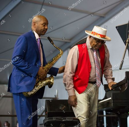 Branford Marsalis helps his father Ellis Marsalis at the piano before the Ellis Marsalis Family Tribute performance in the Jazz Tent during the New Orleans Jazz & Heritage Festival in New Orleans