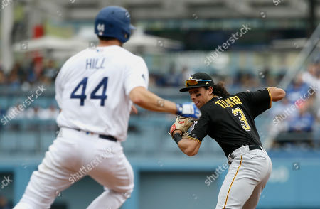 Pittsburgh Pirates shortstop Cole Tucker, right, throws around Los Angeles Dodgers' Rich Hill, left, to get Joc Pederson at first for a double play during the third inning of a baseball game in Los Angeles