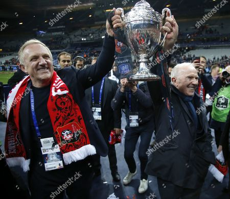 Chairman and CEO of Kering, Francois-Henri Pinault (L), and his father Francois Pinault celebrate with the trophy after Rennes (SRFC) won the French Cup final