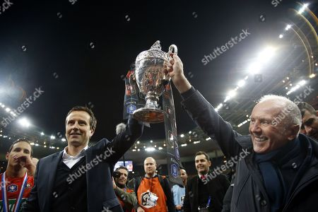French businessman Francois Pinault (R) holds the trophy with Stade Rennais' French head coach Julien Stephan after Rennes (SRFC) won the French Cup final