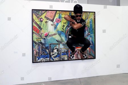 Stock Image of Brazilian artist Carlinhos Brown poses for the photographer next to one of his paintings as he present his art exhibition 'Carlinhos Brown. La mirada que escucha' (Carlinhos Brown. The sight that listens) at the Fundacion Telefonica exhibition center in Madrid, Spain, 29 April 2019. The show featuring 14 big art works by the Brazilian composer, singer and percussionist runs from 01 May to 02 June.