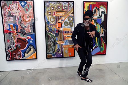 Brazilian artist Carlinhos Brown poses for the photographer next to one of his artworks as he present his art exhibition 'Carlinhos Brown. La mirada que escucha' (Carlinhos Brown. The sight that listens) at the Fundacion Telefonica exhibition center in Madrid, Spain, 29 April 2019. The show featuring 14 big art works by the Brazilian composer, singer and percussionist runs from 01 May to 02 June.