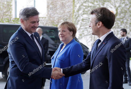 German Chancellor Angela Merkel and the President of France Emmanuel Macron, right, welcome Bosnian prime minister Denis Zvizdic for a meeting of Balkan leaders at the chancellery in Berlin, . German Chancellor Angela Merkel and French President Emmanuel Macron are hosting the meeting to restart deadlocked talks between Serbia and Kosovo
