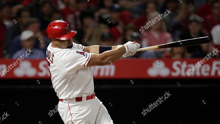 Los Angeles Angels' Albert Pujols follows through after hitting an RBI single during the third inning of a baseball game against the Seattle Mariners, in Anaheim, Calif