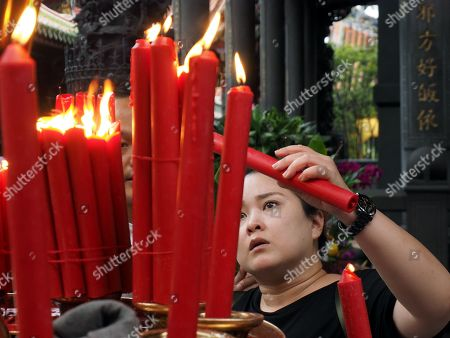 A woman lights a candle at the Longshan Temple in Taipei, Taiwan, 29 April 2019. Starting 01 May, Longshan Temple, Taipei's largest Buddhist temple, will ban burning candles to prevent fire and reduce air pollution. More than 60 per cent of Taiwanese follow Buddhism or Taoism and burn incense and candles at home or in temples.