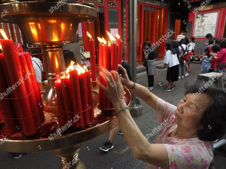 A woman arranges candles at the Longshan Temple in Taipei, Taiwan, 29 April 2019. Starting 01 May, Longshan Temple, Taipei's largest Buddhist temple, will ban burning candles to prevent fire and reduce air pollution. More than 60 per cent of Taiwanese follow Buddhism or Taoism and burn incense and candles at home or in temples.