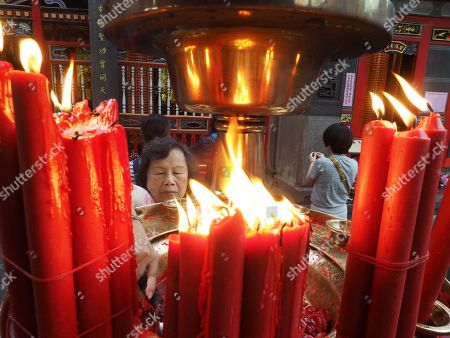 A woman cleans a candle stand at the Longshan Temple in Taipei, Taiwan, 29 April 2019. Starting 01 May, Longshan Temple, Taipei's largest Buddhist temple, will ban burning candles to prevent fire and reduce air pollution. More than 60 per cent of Taiwanese follow Buddhism or Taoism and burn incense and candles at home or in temples.