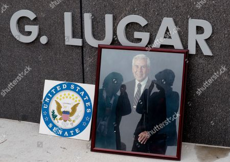 Women are reflected in the glass of photograph Sen. Richard Lugar places at the entrance to the Richard G. Lugar Plaza outside the City-County Building in Indianapolis, . Lugar, 87, died Sunday