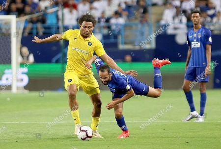 Stock Photo of Al-Taawoun's Leandre Tawamba Kana (L) in action against Al-Hilal's Abdullah Otayf (C) during the Saudi Professional League soccer match between Al-Hilal S.FC and Al-Taawoun FC at King Saud University Stadium in Riyadh, Saudi Arabia, 29 April 2019.