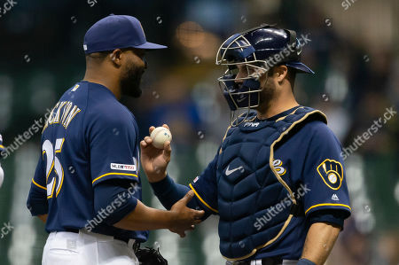 Milwaukee Brewers relief pitcher Jay Jackson #25 is congratulated by Milwaukee Brewers catcher Yasmani Grandal #10 after leaving the game during the Major League Baseball game between the Milwaukee Brewers and the Colorado Rockies at Miller Park in Milwaukee, WI