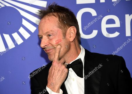 Simon Kirke points to a lipstick mark on his cheek made by his wife at the Film Society of Lincoln Center's 50th anniversary gala at Alice Tully Hall, in New York