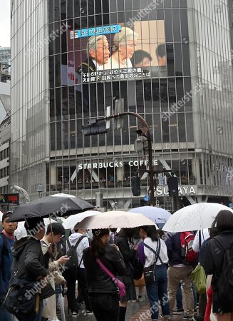 Emperor Akihito and Empress Michiko are seen on a giant screen at Tokyo Shibuya district as Akihito is set to abdicate at 5:00 pm local time, making him the first Japanese monarch to do so in over two hundred years.