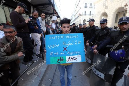 A demonstrator holds a placard, as policemen block the way front of protesters against Former Algerian Prime Minister Ahmed Ouyahia in front of the court of justice in Algiers, Algeria, 30 April 2019.  According to media reports, Ouyahia was questioned today in a widening investigation into alleged corruption in the inner circle of ousted president Abdelaziz Bouteflika.