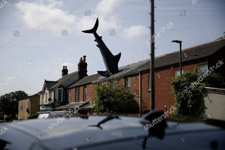 """A fibreglass sculpture known as the Headington Shark and originally called """"Untitled 1986"""", by British sculptor John Buckley stands appearing to crash through the roof of a house in the Headington area of Oxford, England, . The sculpture was commissioned by the American-born owner of the house, radio broadcaster Bill Heine, who died aged 74 earlier this month"""