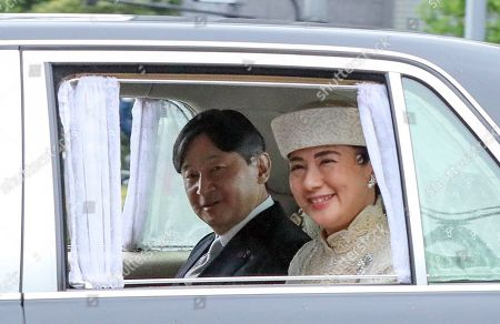 Japan's Crown Prince Naruhito (L) and Crown Princess Masako arrive at the Imperial Palace in Tokyo, Japan