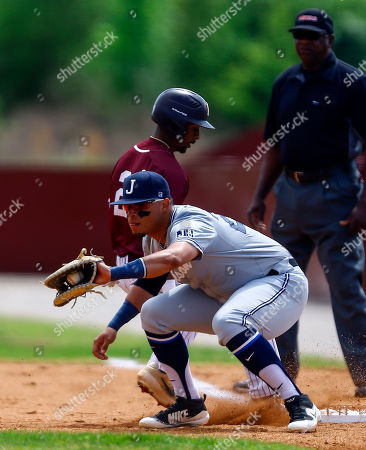Alabama A&M's Jonathan Smith beats the throw to Jackson State first baseman Raul Hernandez as he gets back to first during an NCAA college baseball game, in Huntsville, Ala