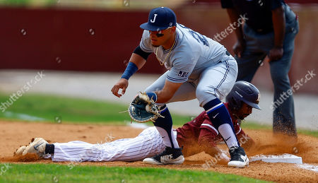 Alabama A&M's Jonathan Smith beats the throw to Jackson State first baseman Raul Hernandez as he dives back to first during an NCAA college baseball game, in Huntsville, Ala