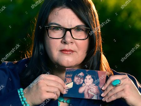"""Stock Picture of Jennifer """"Jenn"""" Carson 40, of Moreno Valley, daughter of convicted serial killer Michael Bear Carson, holding a 1975 photo of her with her father at the Shadow Mountain Park, Moreno Valley, Calif. Carson is fighting the release of her father and his current wife Suzan Carson the so-called San Francisco Witch Killers who are now eligible for parole."""