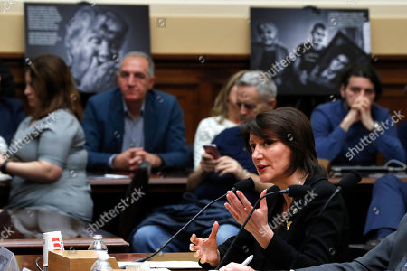 With photographs of the families of people who went missing during the Kosovo War in the background, former Kosovo president Atifete Jahjaga testifies during a House Foreign Affairs Committee on Kosovo's Wartime Victims, on Capitol Hill in Washington