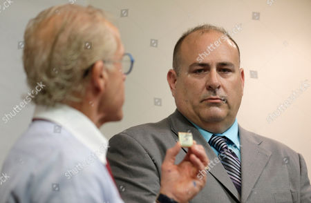 Attorney Jeff Anderson, left, holds up a physical fitness badge used by the Boy Scouts of America as Richard Halvorson looks on during a news conference in Newark, N.J., . Halvorson is alleging sexual abuse in a lawsuit filed against the Boy Scouts of America. The abuse occurred under the guise of trying to earn the fitness badge when Halvorson was an 11-year-old boy scout