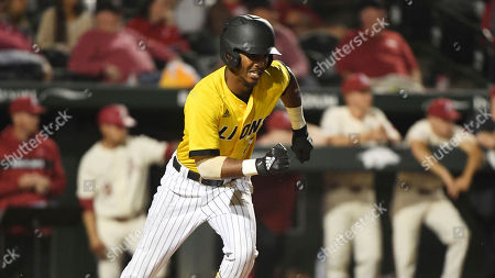 Arkansas Pine Bluff baserunner Justin Robinson tries to beat the throw to first base against Arkansas during an NCAA college baseball game, in Fayetteville, Ark