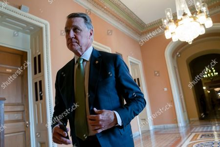 Sen. David Perdue, R-Ga., returns to the chamber following a meeting with fellow Republicans, at the Capitol in Washington