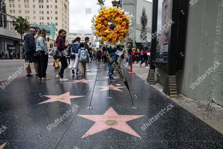 People pass a wreath placed to honor the memory of late US director John Singleton on behalf of the Hollywood community by the Hollywood Historic Trust, in Hollywood, California, USA, 30 April 2019. According to media reports, John Singleton has died, citing his family on 29 April. The 51-year-old writer and director of 'Boyz n the Hood' had suffered a stroke two weeks ago and was in a coma.