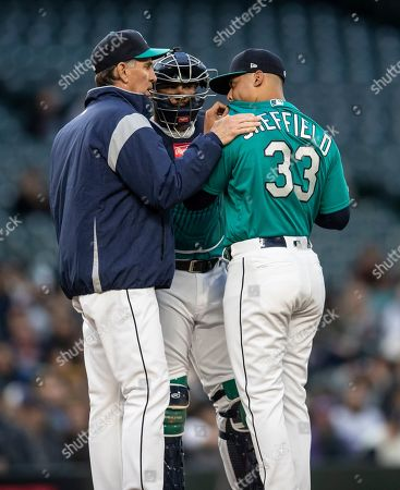 Paul Davis, Omar Narvaez, Justus Sheffield. Seattle Mariners pitching coach Paul Davis, left, catcher Omar Narvaez, center, and relief pitcher Justus Sheffield meet at the mound during a baseball game against the Texas Rangers, in Seattle. The Mariners won the game 5-4 in 11 innings