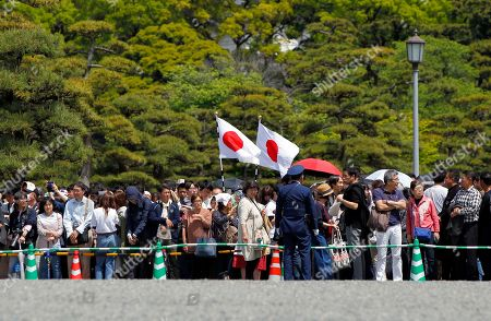 People gather around the Imperial Palace where Crown Prince Naruhito is to be enthroned to become new Japanese Emperor, in Tokyo. Japan has new Emperor Naruhito to perform his first ritual after succeeding the Chrysanthemum Throne from his father Akihito who abdicated the night before. (AP Photo/Eugene Hoshiko