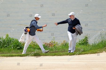 Virginia's David Morgan celebrates with Head Coach Bowen Sargent after getting a birdie on seventeen during the Atlantic Coast Conference Championship golf tournament, in New London, N.C