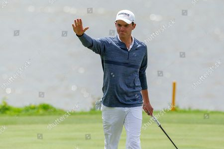 Virgina's David Morgan waves to spectators after he makes his putt for birdie on the seventeenth green during the Atlantic Coast Conference Championship golf tournament, in New London, N.C