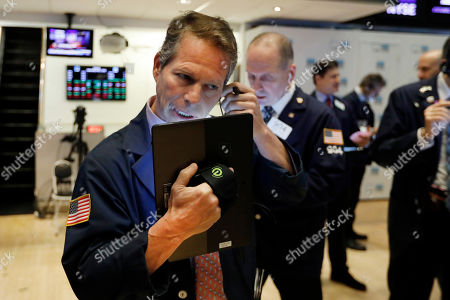 Trader Robert Charmak, left, works on the floor of the New York Stock Exchange, . Stocks are opening higher on Wall Street after several big U.S. companies reported earnings that were better than analysts were expecting