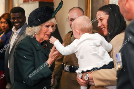 Stock Image of Camilla Duchess of Cornwall meeting one year old Cara May Campbell and mother Sarah Campbell as she attends the medals parade of the 4th Battalion The Rifles at the New Normandy Barracks in Aldershot.