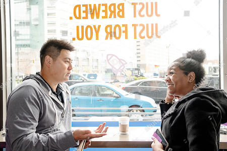 IMAGE DISTRIBUTED FOR EXPERIAN - John Kim, 26 (left) from Irvine, CA, speaks with Redford, MI resident Shania Hale, 22 (right) about financial literacy and how the Experian Boost program can help her credit score at the Roasting Plant at the #BoostAmerica campaign launch on in Detroit
