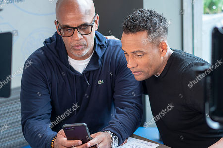 Grosse Pointe Park resident Matt Evans, 48, (left) and actor Hill Harper (right) watch on Evan's mobile phone as he enters his information on the Experian Boost website at the Roasting Plant in Detroit at the #BoostAmerica campaign launch on in Detroit