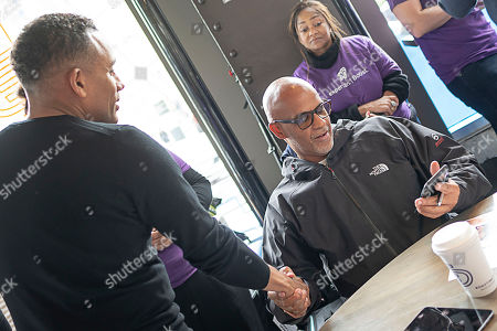 Actor, author, and owner of The Roasting Plant Hill Harper (left), greets Grosse Pointe Park, MI resident Matt Evans, 48, (right) as Evans enters his information on the Experian Boost website at the Roasting Plant at the #BoostAmerica campaign launch on in Detroit