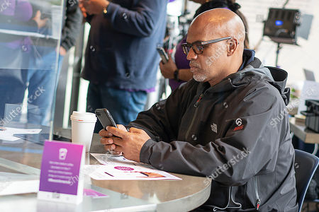 Grosse Pointe Park resident Matt Evans, 48, enters his information on the Experian Boost website at the Roasting Plant at the #BoostAmerica campaign launch on in Detroit