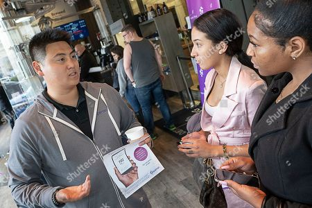 John Kim, 26, from Irvine, CA (left) speaks with Racheal Mootz, 22, from Detroit (center), and Shania Hale, 22, from Redford (right) about Experian Boost and how it affects your credit score at the Roasting Plant at the #BoostAmerica campaign launch on in Detroit