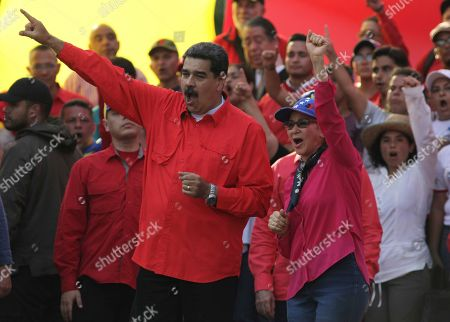 Venezuela's President Nicolas Maduro, center left, and his wife Cilia Flores, center right, wave at supporters during a rally in Caracas, Venezuela, . Opposition leader Juan Guaidó called for Venezuelans to fill streets around the country Wednesday to demand President Nicolás Maduro's ouster. Maduro is also calling for his supporters to rally