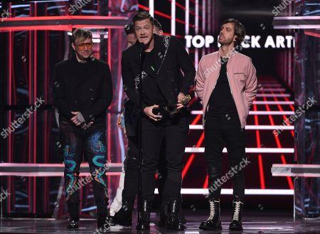 Ben McKee, Dan Reynolds, Wayne Sermon. Ben McKee, from left, Dan Reynolds, and Wayne Sermon of Imagine Dragons, accept the award for top rock artist at the Billboard Music Awards, at the MGM Grand Garden Arena in Las Vegas