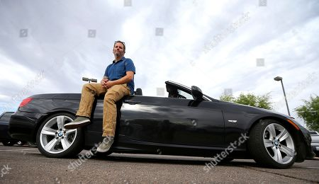 Chris Williamson poses for a photo sitting on his car in Phoenix. When Williamson was in the market for a new family car, a timely ad and conversations with a co-worker convinced him to try something out of the ordinary. He bought the BMW 3 Series convertible and covers the payments by renting it to strangers on a peer-to-peer car sharing app called Turo. It allows his family of seven to have a nicer car, essentially for free