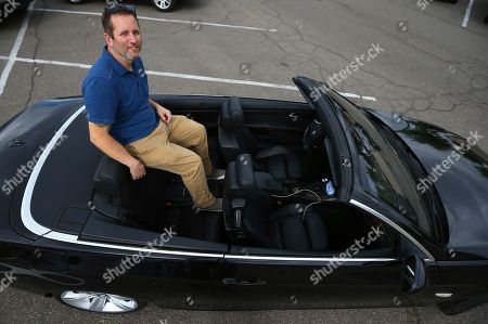 Chris Williamson hangs sits in his car, in Phoenix. Williamson rents his car on Turo, a car-sharing platform that is basically Airbnb for rental cars, but several legislatures and traditional car rental companies are trying to have Turo customers pay the same taxes Turo customers currently do not have to pay