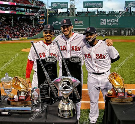 Boston Red Sox's Mookie Betts, left, J.D. Martinez, center, and Jackie Bradley Jr. stand with their various 2018 awards including Silver Sluggers, Gold Gloves and the AL MVP before a baseball game between the Boston Red Sox and the Toronto Blue Jays, at Fenway Park in Boston