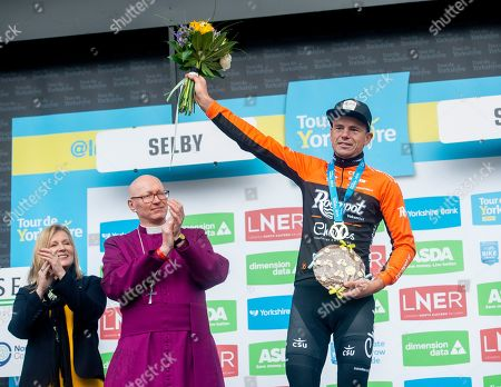 The Roompot-Charles rider Jesper Asselman celebrates with the Bishop of Selby John Thompson (2L) winning the first stage of the the Tour de Yorkshire 182,5 km between Doncaster and Selby, in Selby, Britain, 02 May 2019.