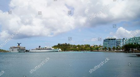 The Freewinds cruise ship, right, is docked in the port of Castries, the capital of St. Lucia, . Authorities in the eastern Caribbean island have quarantined the ship after discovering a confirmed case of measles aboard