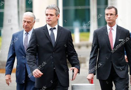 Mickael Behn, center, and Javier Garcia-Bengochea, right, walk out of federal court with attorney Bob Martinez, left, after filing lawsuits against Carnival Cruise Line, that has been using their former properties in Cuba, in Miami. Behn and Garcia-Bengochea, the heirs of families that owned ports in Havana and Santiago de Cuba now being used to dock cruise ships that began traveling to Cuba in 2016 under President Barack Obama's detente with the island