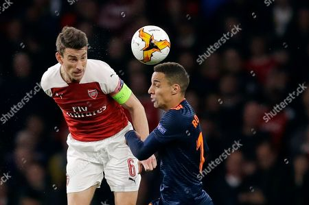 Arsenal's Laurent Koscielny, left, challenges for the ball with Valencia's Rodrigo during the Europa League semifinal first leg soccer match between Arsenal and Valencia at the Emirates stadium in London